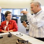 University of Wisconsin-Madison Chancellor Rebecca Blank (center) and Ian Robertson (left), dean of the College of Engineering, listen as George Broughton (right), director of Advanced Engineering and Innovation BRP / Evinrude, talks about product innovations during a tour of the company's facilities in Sturtevant, Wis., on Oct. 18, 2016. (Photo by Bryce Richter / UW-Madison)