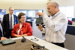 University of Wisconsin-Madison Chancellor Rebecca Blank (center) and Ian Robertson, dean of the College of Engineering (left) listen as George Broughton, director of Advanced Engineering and Innovation BRP / Evinrude (right), talks about engine innovations during a tour of the company's facilities in Sturdevant, WI on Oct. 18, 2016. (Photo by Bryce Richter / UW-Madison)