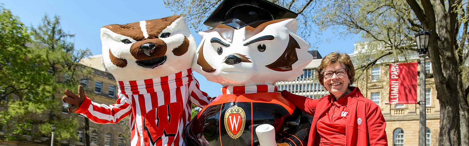 "Bucky Badger and Chancellor Rebecca Blank stand next to the ""Graduation Bucky"", a ""Bucky on Parade"" statue."