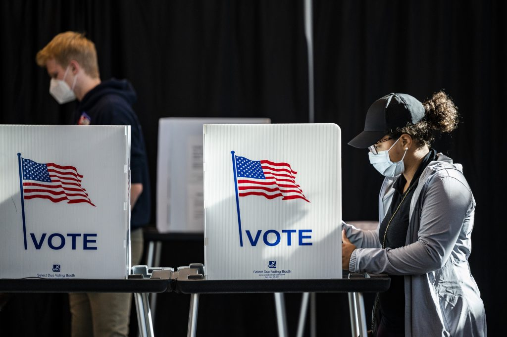 Photo of two students at voting booths casting their ballots.